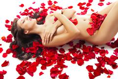 slim woman lying on red roses petals over white - stock photo