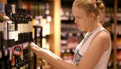 Woman shopping for alcohol in a bottle store Stock Footage