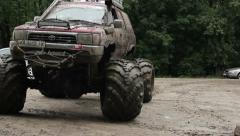 Large bigfoot driving away, wheels and glasses in dirt mud Stock Footage