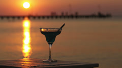 Tropical cocktail overlooking a sunset ocean Stock Footage