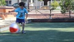 Little Boy Runs to Kick Beach Ball Stock Footage
