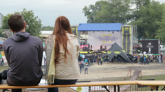 Young couple watching show sitting bench, rock concert contest Stock Footage