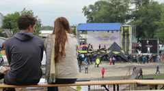 Young couple sitting on bench watching big show concert gig Stock Footage