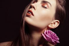 Portrait of beautiful brunette woman with rose - stock photo