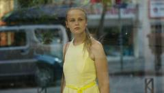Young girl passing by a shoe shop Stock Footage