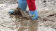 Stock Video Footage of Child feet in rubber boots walk puddle dirt, construction site