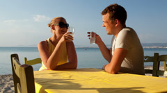 Young couple enjoying drinks at the seaside - stock footage