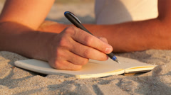 Man writing in his diary at the beach Stock Footage