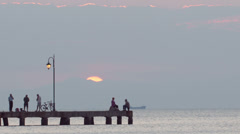 People relaxing on a pier at sunset. Ship is passing by Stock Footage
