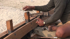 Master with primitive tools build wooden boat near Ganges river, Varanasi Stock Footage