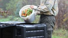 Compost - man throws kitchen scraps into a composter. Stock Footage