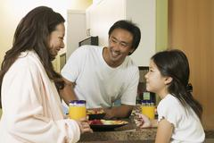 Family Enjoying Breakfast in kitchen Stock Photos
