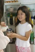 Mother Pouring Milk For Daughter in kitchen by open fridge close up of daughter - stock photo