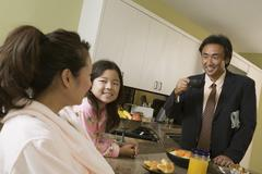 Family At Breakfast Table With Father Ready For Work - stock photo