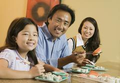 Family Eating Sushi At Home Stock Photos