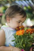 Young girl smelling marigold flowers in plant nursery close up - stock photo