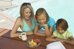 Two Girls (7-9) and Grandmother Watching portable television by swimming pool. - stock photo