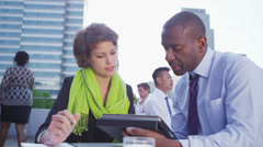 Business man and woman having a meeting on an open air city roof terrace - stock footage