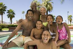 Girl (5-6) boy (7-9) boy (10-12) with parents and grandparents at swimming pool - stock photo