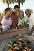 Senior couple and mid-adult couple looking at camcorder at outdoor barbecue. - stock photo