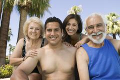 Senior couple and mid-adult couple outdoors front view portrait. - stock photo