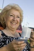 Senior Woman outdoors listening to portable music player holding cup smiling. Stock Photos