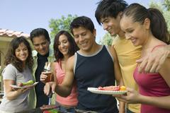 Stock Photo of Group Of Casual Friends Enjoying A Barbecue