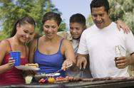 Stock Photo of Cheerful Family Around The Grill At Picnic