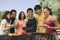Stock Photo of Friends Gathered Around Grill At Picnic