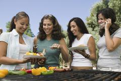Group Of Four Females Enjoying A Barbecue - stock photo