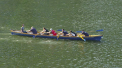 Rowing crew of mixed ages traveling down the River Thames Stock Footage