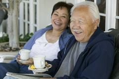 Senior couple drinking tea on porch smiling - stock photo
