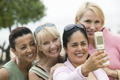 Group of middle-aged women photographing themselves with a mobile phone Stock Photos