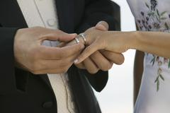 Groom placing ring on brides finger (close-up) - stock photo