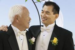 Groom with father outdoors (close-up) - stock photo