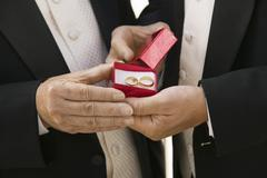 Groom and father holding wedding rings (close-up) - stock photo