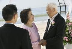 Groom with parents at beach wedding - stock photo