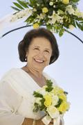Mother of bride with bouquet outdoors (portrait) - stock photo