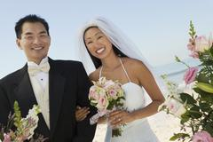 Bride and Groom with flowers on beach (portrait) - stock photo