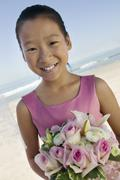 Young Bridesmaid with flowers on beach (portrait) - stock photo
