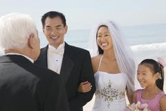 Bride and Groom with family by ocean - stock photo