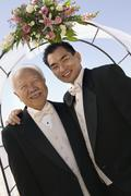 Groom with father under archway outdoors (portrait) - stock photo