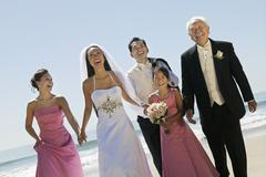 Bride and Groom with family on beach (portrait) - stock photo