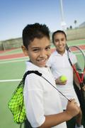 Young boy and girl with tennis equipment on tennis court focus on boy portrait - stock photo