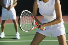 Midsection Of Mixed Doubles Tennis Players On Court - stock photo