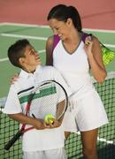 Mother and son by net on tennis court high angle view - stock photo