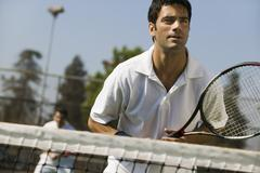 Male doubles tennis players waiting for serve front view focus on foreground Stock Photos