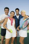 Four mixed doubles tennis players by net at tennis court portrait Stock Photos