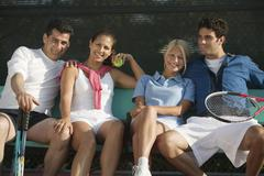 Four mixed doubles tennis players sitting on bench at tennis court portrait Stock Photos