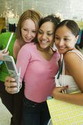 3 Girl friends Posing for Camera Phone Picture in clothing store - stock photo